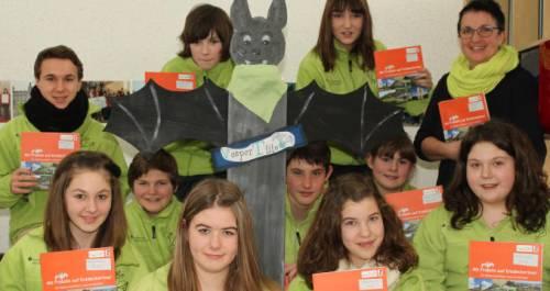 Die Jungen und Mädchen der Schülerfirma Vespertilio zeigen Exemplare ihres Hunsrück-Reiseführers für Kinder. In der Mitte steht ein Holzmodell der Fledermaus Fridolin. TV-Foto: Christoph strouvelle
