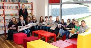 Die Schülerinnen der Bibliotheks-AG und die Bibliotheksleiterin Frau Ruhk mit Bibliotheksbesuchern beim Zeitunglesen (gestiftet vom Lesepatenprojekt des Trierischen Volksfreunds und der Sparkasse)