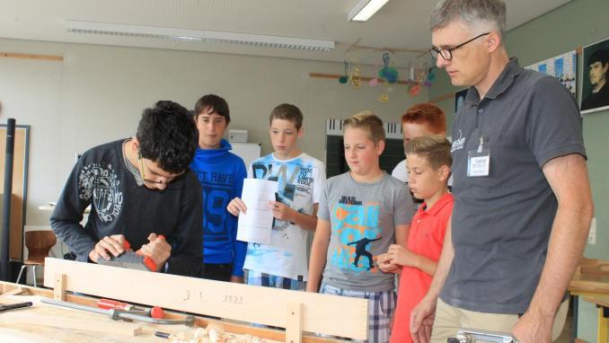 Heinz Bauer vom Morbacher Betrieb Treppenbau Bastian zeigt einem Schüler, wie man mit einem Hobel arbeitet. TV-Foto: Christoph Strouvelle